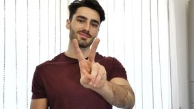 Man doing peace or victory sign with two fingers. Attractive young man doing peace or victory sign with two fingers, indoor at home in his living-room stock video