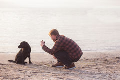 Man doing photo of his dog. Young caucasian male walking with dog on the morning beach, sunset on the sea or ocean and man with black labrador puppy Royalty Free Stock Photo