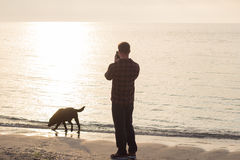 Man doing photo of his dog. Young caucasian male walking with dog on the morning beach, sunset on the sea or ocean and man with black labrador puppy Royalty Free Stock Images