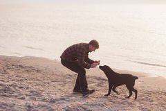 Man doing photo of his dog. Young caucasian male walking with dog on the morning beach, sunset on the sea or ocean and man with black labrador puppy Stock Photo
