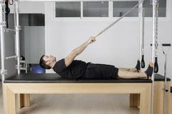 Man doing pilates in cadillac. Royalty Free Stock Photography