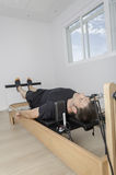 Man doing pilates in cadillac. Stock Images