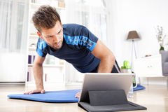 Man Doing Planking While Watching Movie on Tablet Stock Photography