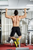 Man doing pull-ups. Fitness man doing pull-ups in a gym for a back workout Royalty Free Stock Photography