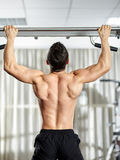Man doing pull-ups. Fitness man doing pull-ups in a gym for a back workout Stock Photos