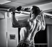 Man doing pull-ups in the gym. Monochrome toned Stock Photos