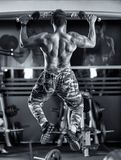 Man doing pull-ups in the gym. Monochrome toned Royalty Free Stock Photos