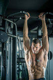Man doing pull ups in gym Stock Photography