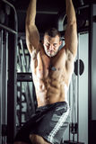 Man doing pull ups in gym Stock Photo