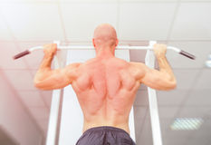 Man doing pull ups with well shaped muscles Stock Photography