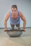 Man doing push-up on bosuball. Portrait of handsome man doing push-up on bosuball in gym Royalty Free Stock Photography