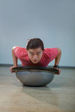 Man doing push-up on bosuball. Portrait of handsome man doing push-up on bosuball in gym Stock Photo