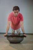 Man doing push-up on bosuball. Portrait of handsome man doing push-up on bosuball in gym Royalty Free Stock Photos