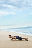 Man Doing Push Up Exercise On Beach. Body Exercising Concept Royalty Free Stock Images
