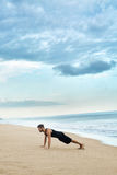 Man Doing Push Up Exercise On Beach. Body Exercising Concept Stock Photo