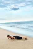 Man Doing Push Up Exercise On Beach. Body Exercising Concept Royalty Free Stock Photography