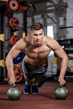 Man doing push-up exercise with dumbbell Royalty Free Stock Image