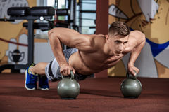 Man doing push-up exercise with dumbbell. At crossfit gym Royalty Free Stock Image