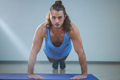 Man doing push-up on exercise mat. Portrait of man doing push-up on exercise mat in gym Stock Photography