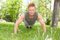 Man doing a push up in park. Caucasian man doing a push up in park against blur background Stock Photography