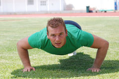 Man doing push-ups. Young man doing push-ups outdoors Stock Images