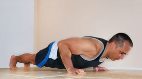 Man Doing Push Ups. Strong man in tank top doing push ups on the floor Royalty Free Stock Photography