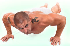 Man doing push-ups. The perfect muscular male doing push-ups stock image