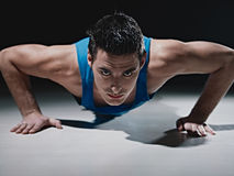 Man doing push-ups on black background Stock Photo