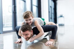 Man doing push ups with boy on his back royalty free stock images