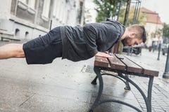 Man doing push-ups on a bench. Stock Photos
