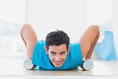 Man doing push ups with dumbbells in fitness studio Royalty Free Stock Image