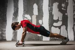 Man doing push ups on dumbbells  the wall backdrop Royalty Free Stock Image
