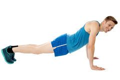 Man doing push-ups exercise in gym. Young smiling fitness man doing push ups on floor royalty free stock images
