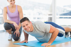 Man doing push ups with female trainer Stock Photo