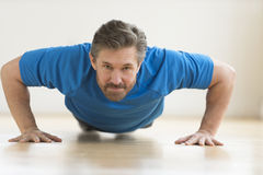 Man Doing Push-Ups On Floor At Home Stock Photos