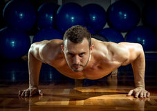 Man doing push-ups in gym. Young adult man doing push-ups in gym Royalty Free Stock Photos