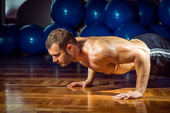 Man doing push-ups in gym Stock Photography