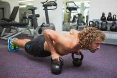 Man doing push ups with kettle bells in gym Stock Image