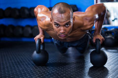Man doing push-ups with kettlebells Royalty Free Stock Photo
