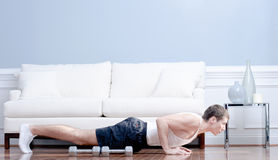 Man Doing Push-ups in Living Room Stock Photos