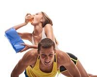 Man doing push ups but woman eating Royalty Free Stock Photos