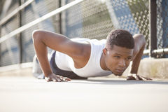 Man doing push ups. A young man doing push ups on concrete Stock Images