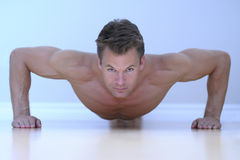 Man doing pushup. Topless male model performs pushup on floor Royalty Free Stock Image