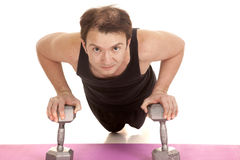 Man doing pushup on weights facing Stock Photography