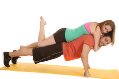 Man doing pushup woman on back leg up Royalty Free Stock Photos