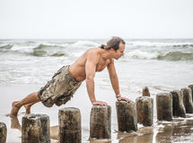 Man doing pushups on the beach Royalty Free Stock Images