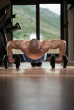 Man Doing Pushups On Dumbbells Stock Photography