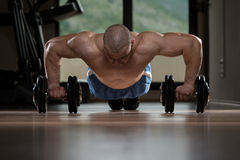 Man Doing Pushups On Dumbbells Royalty Free Stock Photography