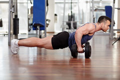 Man doing pushups on dumbbells stock photos
