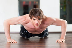 Man doing pushups in gym Stock Images